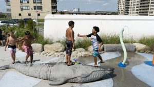 Children playing on a whale sculpture at Sandpiper Playground in Rockaway, Queens.